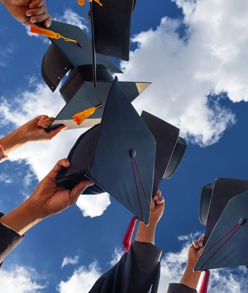 Image of graduation caps against a partly cloudy sky