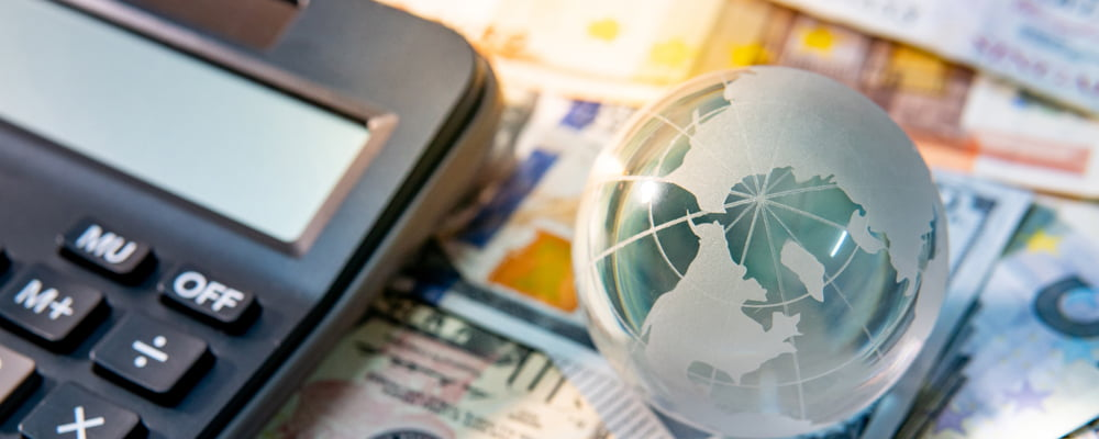 Image of a calculator, international currency and a small globe